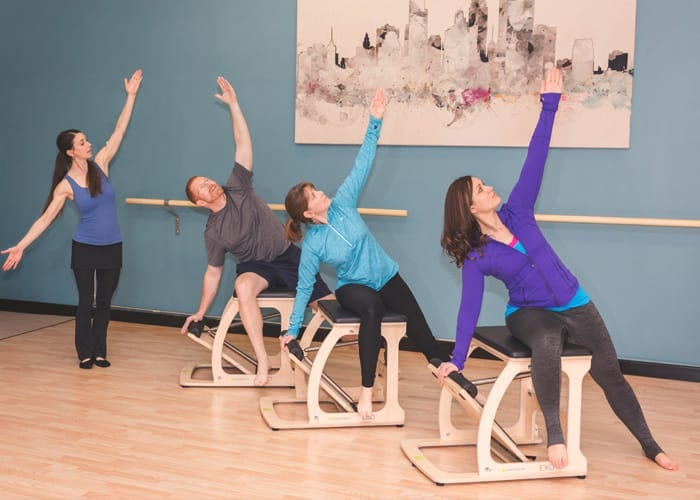 A group of students doing Pilates in a group class utilizing Pilates chair and other equipment