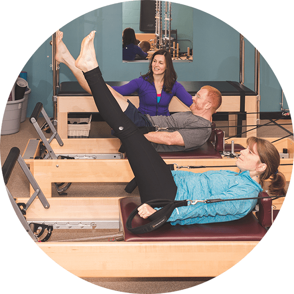 Man and woman doing Pilates together during a private session