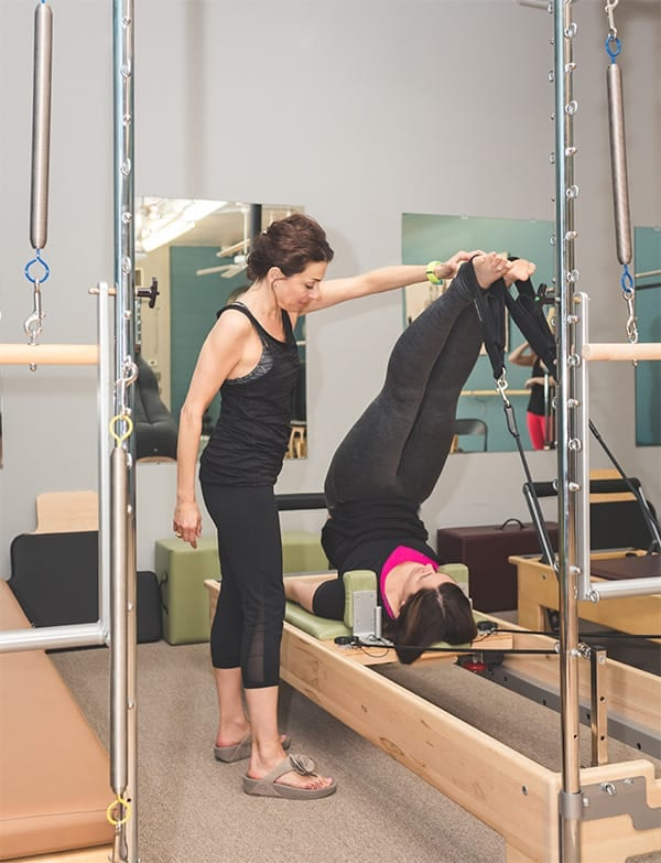 Pilates teacher spotting a client during an exercise on the Reformer